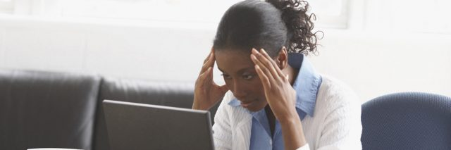 Businesswoman sitting in an office with her hands on her forehead