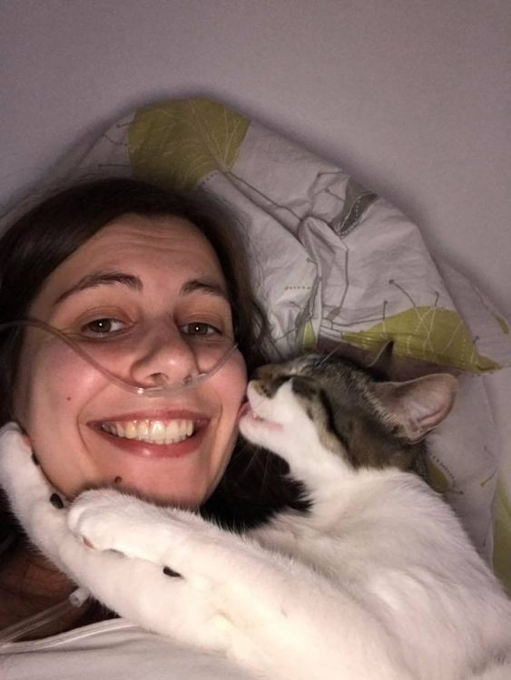 woman lying in bed cuddling with her cat with an oxygen tube in her nose