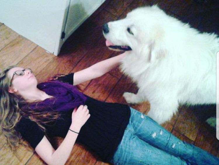 woman lying on the floor petting a big white dog