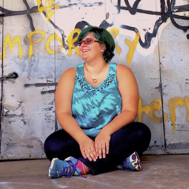 woman sitting outside in workout gear in front of a concrete wall