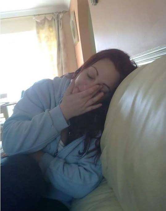 woman sitting on the couch wiping her eyes
