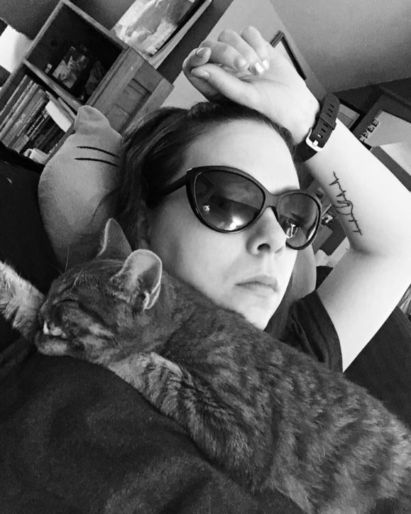black and white photo of woman lying on couch wearing sunglasses and holding her cat