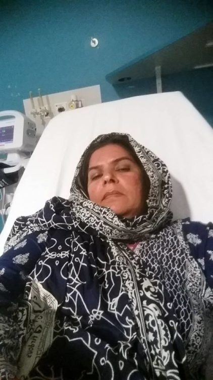 woman wearing a hijab and lying in a hospital bed