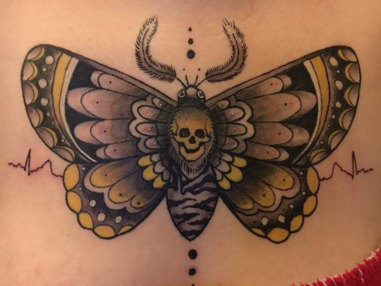 tattoo of a moth with a skull at the center