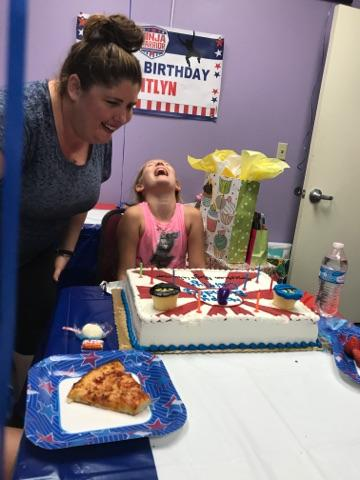 woman blowing out birthday cake candles with her daughter