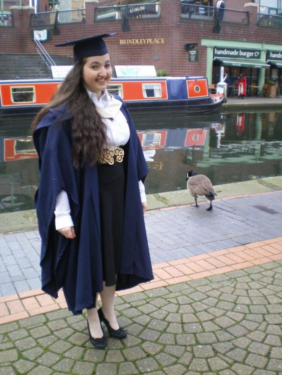 woman standing by a river in her graduation cap and gown
