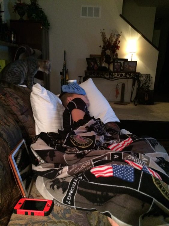 boy lying on couch with an ice pack on his head