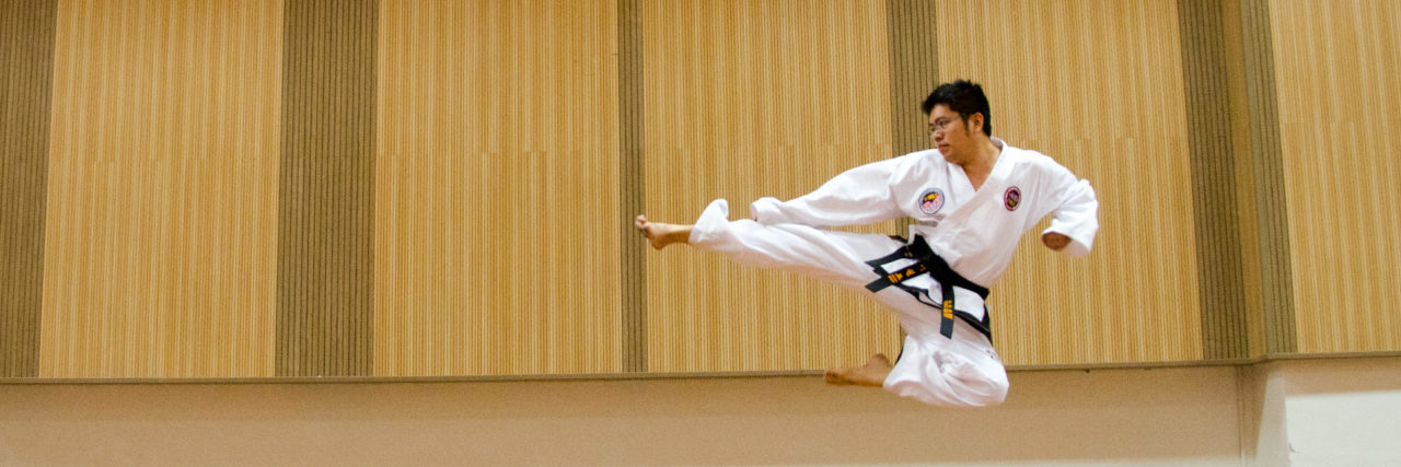 contributor image of asian man kicking through air