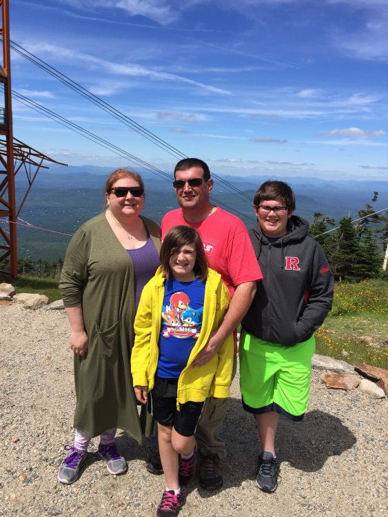 family standing together on a mountain