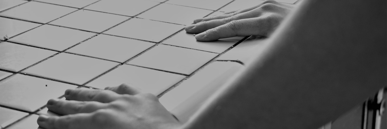 black and white photo of woman's hands gripping tiled counter