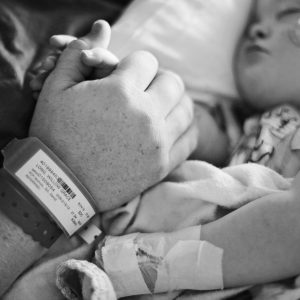 Black and white photo of little girl in hospital bed holding on to parent's hand while she sleeps