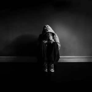 black and white photo of person in darkness looking depressed against wall Michelle Tuttle - MCT Photography