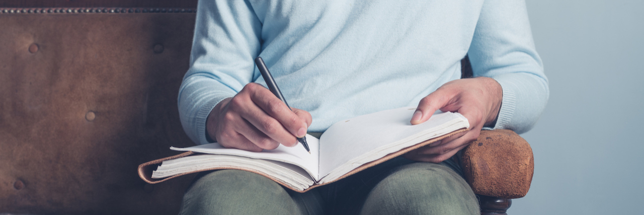 a man writing in notebook