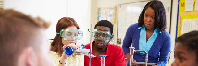High school students and the teacher in a chemistry class.