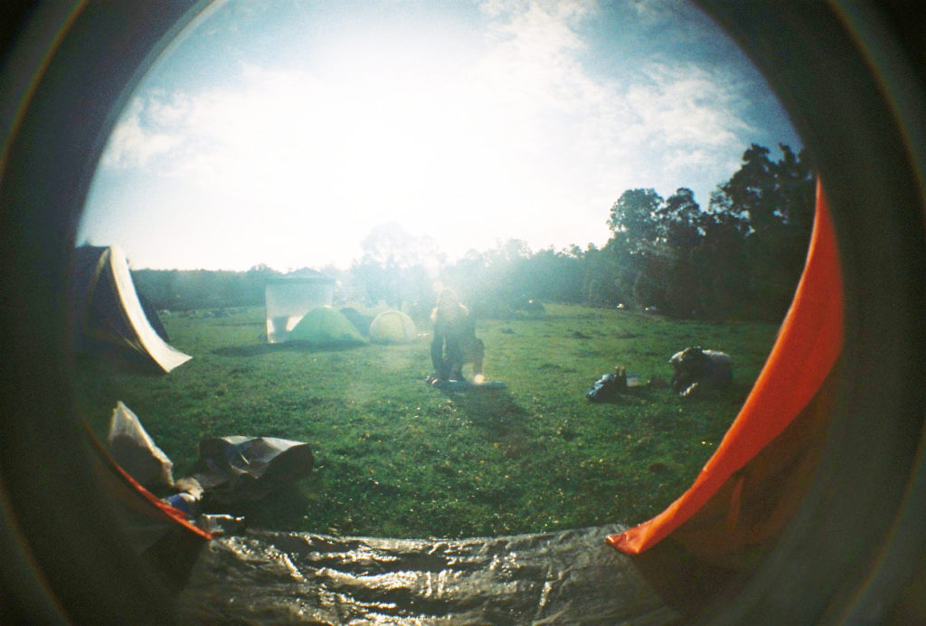 fisheye lens photo of woman packing up tent in sunshine