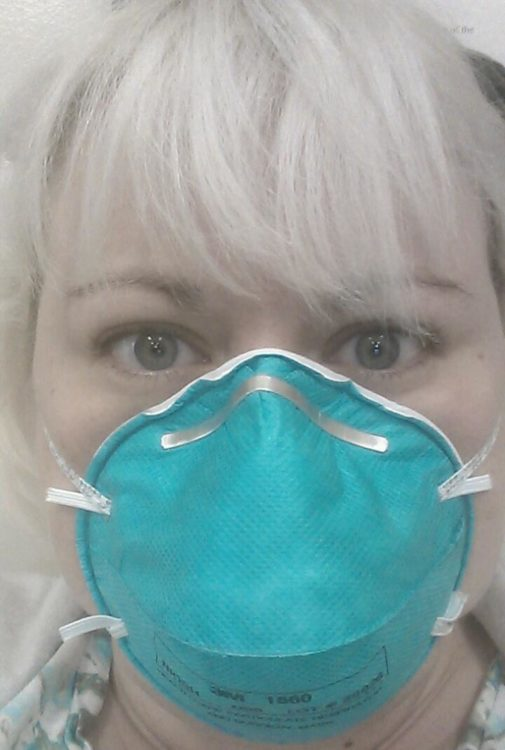 A woman wearing a medical face mask.