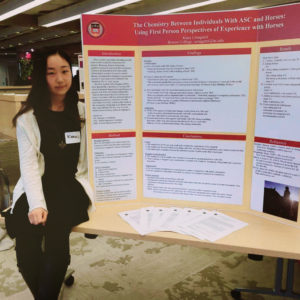 Kana with her conference presentation poster on the topic of Asperger's and horses.
