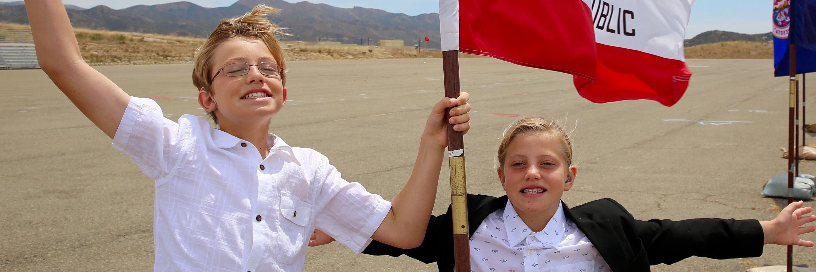 Two kids wearing white shirts and waving a flag.