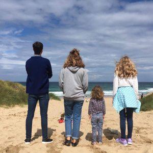 four kids standing on beach looking at ocean
