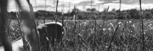 black and white photo of foot in grass with flower high contrast