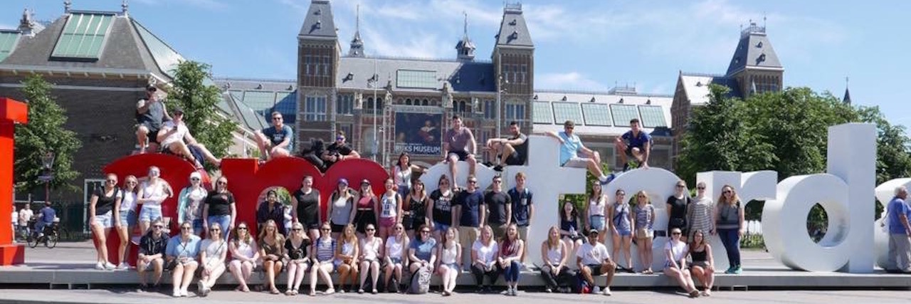 "group sitting in front of the 'I amsterdam"" sign"