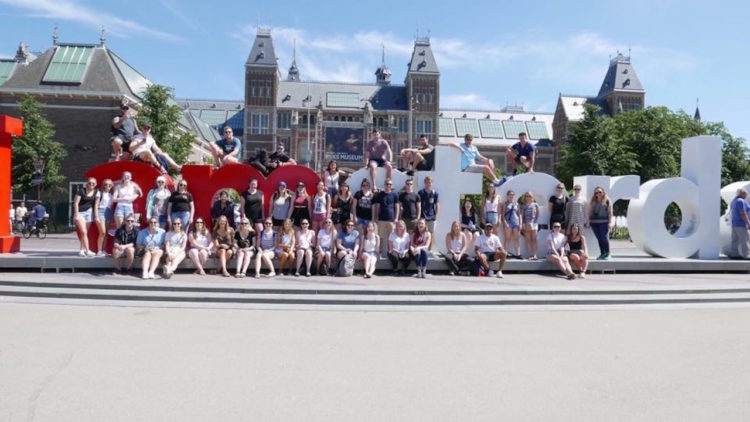 """group sitting in front of the 'I amsterdam"""" sign"""