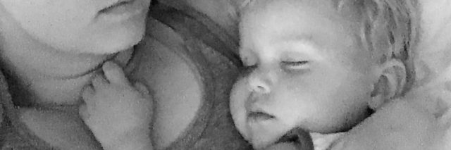 black and white photo of woman holding baby asleep