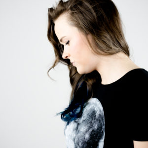 young woman against grey background looking down upset