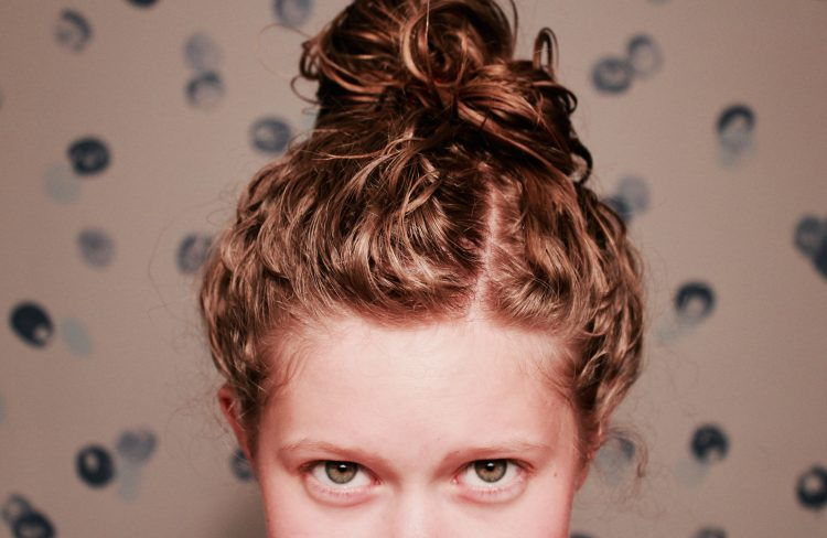 photo of woman's eyes with her hair in a bun