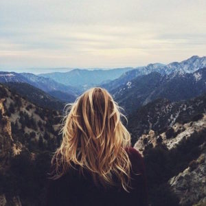 back of woman's head looking out over mountains and valleys