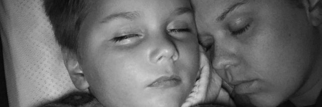 Black and white photo of mom laying with son, both have eyes closed