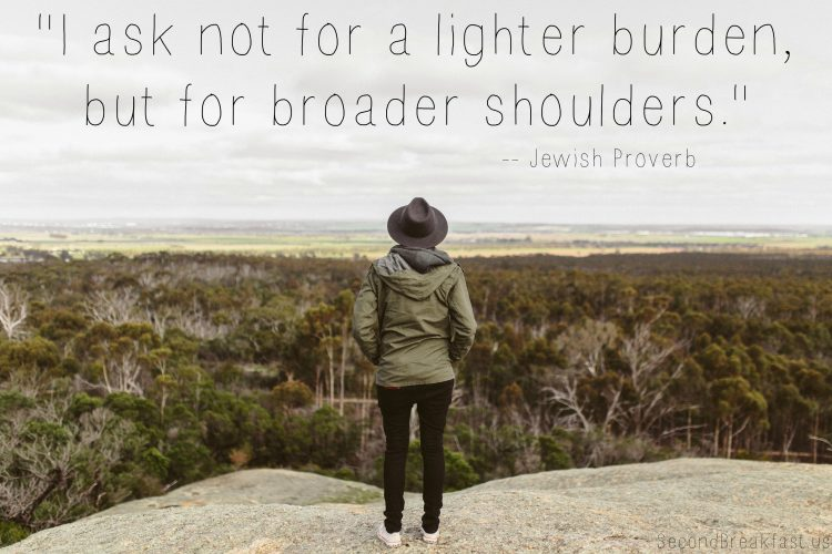 "woman standing on hill overlooking landscape with the text ""I ask not for a lighter burden, but for bigger shoulders."""