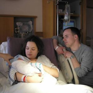 couple at hospital, mom in bed holding baby born with Down syndrome