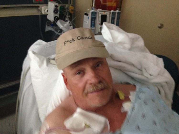 cancer patient in hospital bed with hat on