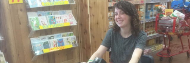 The writer in an electric wheelchair at a store.