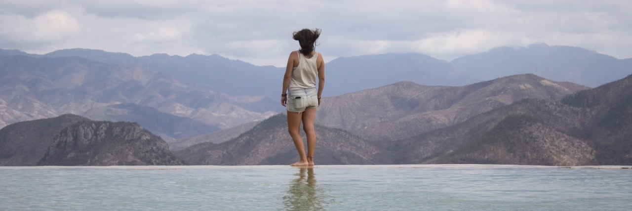 young woman standing on edge of water with mountains in background