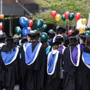graduate students wearing their caps and gowns at a ceremony