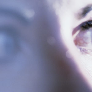 Close up portrait of woman's eye looking anxious.