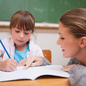 Girl doing school work and teacher at eye level helping
