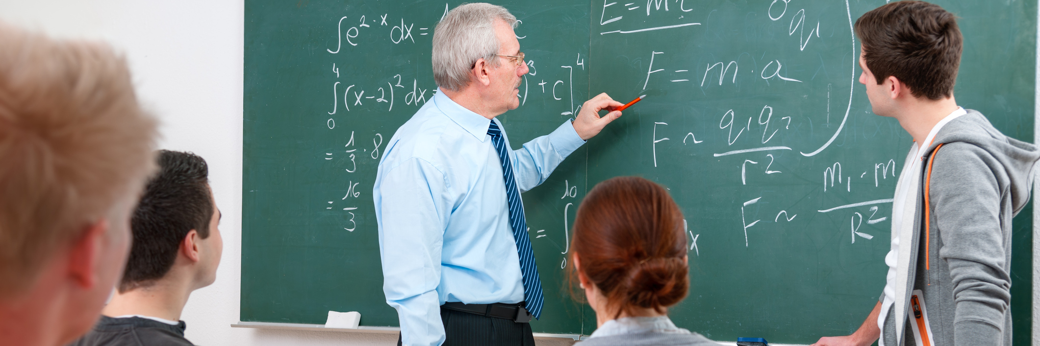 professor writing on chalkboard and teaching students
