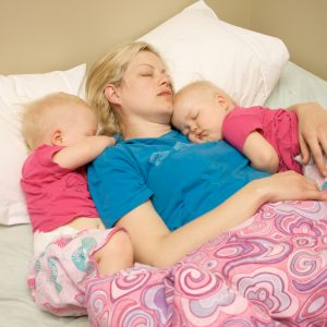 A young mom napping with her twins.