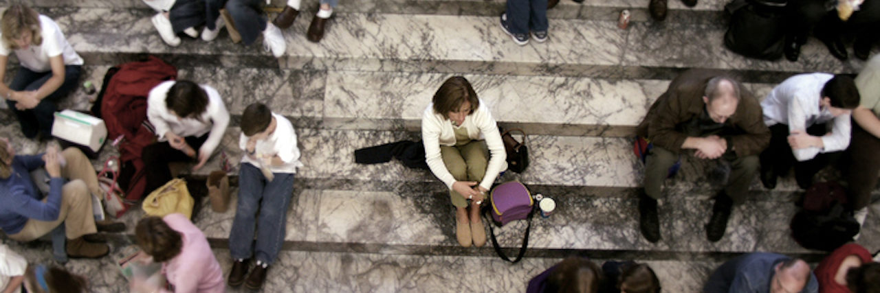 person sitting alone on steps around crowd of people