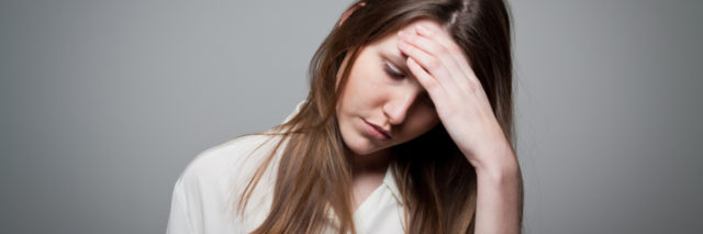 young woman against gray background with hand to head looking stressed and anxious