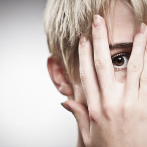 young woman with short blonde hair peeking through fingers