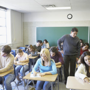 Male lecturer looking at students writing in a classroom