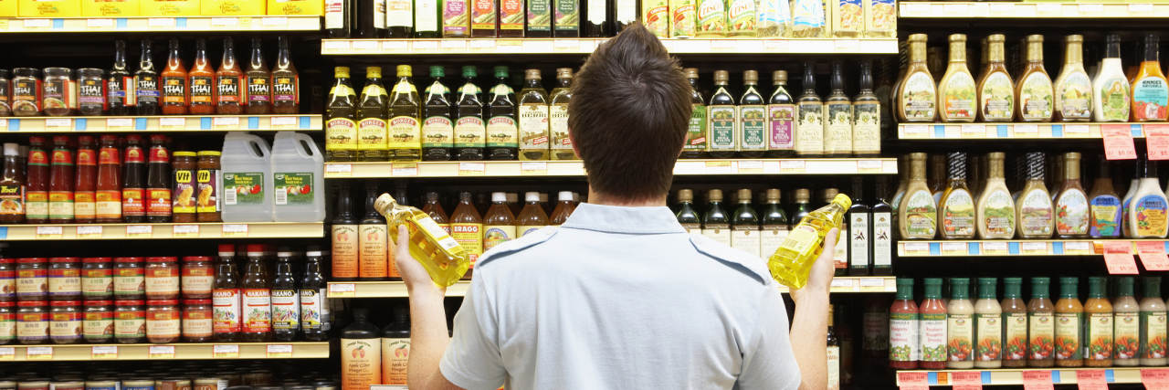 Young man looking at bottles in grocery store.