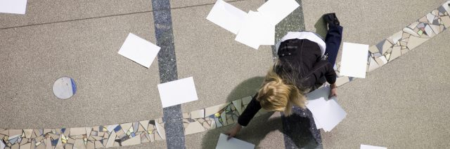 overhead view of blonde business woman in hall picking up scattered papers