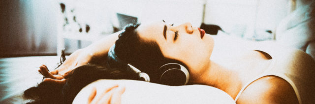Asian woman lying in bed wearing headphones.