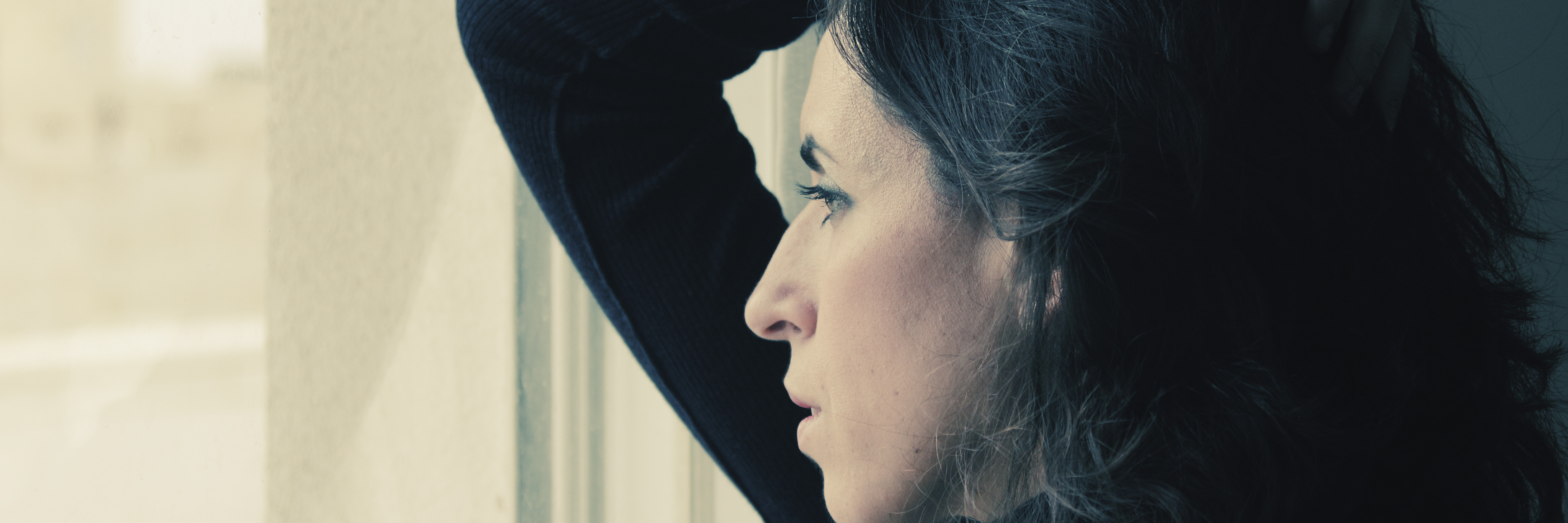 woman stands in front of the window