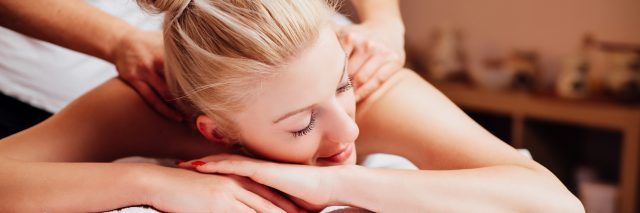 young blonde woman lying face down having massage at salon